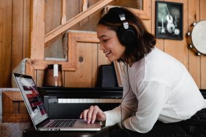 A woman with headphones using a laptop